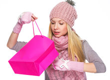 Curious girl in winter clothes looking into shopping bag Stock Photo
