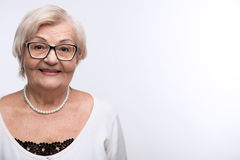 Curious granny looking through her glasses Royalty Free Stock Photo