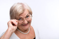 Curious granny looking through her glasses Stock Photography