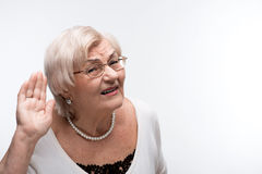 Curious granny trying to hear something. Shameless eavesdropper. Portrait of curious elderly woman holding hand by her ear and struggling to hear something while stock image