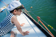 Curious handsome little boy in a captain`s hat peeking over the side of the boat Royalty Free Stock Image