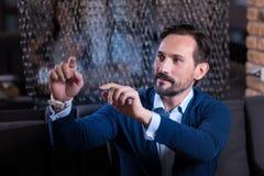 Curious handsome man using virtual sensory panel Royalty Free Stock Image