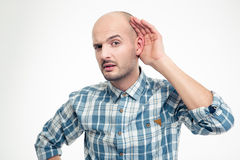 Curious handsome young man in plaid shirt overhearing rumors Royalty Free Stock Photography