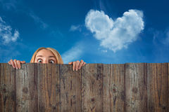 Curious hide woman / girl, cloud heart shape, blue sky background Royalty Free Stock Image