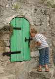 Curious kid. Little boy trying to peek through a small ancient castle door Stock Photo