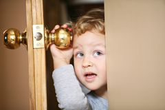 Curious kid. Kid is looking throught the opened door Royalty Free Stock Images