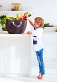 Curious kid getting out a fruit from shopping bag full of food. Curious kid, young boy getting out a fruit from shopping bag full of food Stock Image