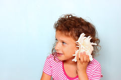 Curious kid listen to seashell. discovery and learning concept Royalty Free Stock Image