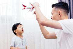 Curious kid looking at the plane toy and playing with father. Asian family playing toys together at home. stock photo
