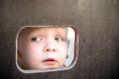 Curious kid spying through the hole in the wooden wall on playground.  royalty free stock photography