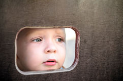 Curious kid spying through the hole in the wooden wall on playground.  royalty free stock photo