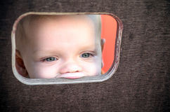 Curious kid spying through the hole in the wooden wall on playground.  royalty free stock photos
