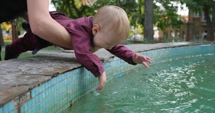 Curious kid trying to touch fountain water at nature. In park stock video footage