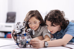 Curious kids playing with robot at school. Enjoying electronic robot together . Delighted happy smiling children sitting at school and having science class while Stock Photography