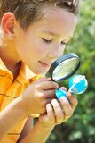 Curious lad. Portrait of cute schoolboy looking at small globe model through spy glass in natural environment Stock Photography
