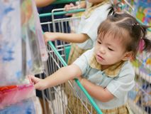 Curious little Asian baby girl in a shopping trolley irresistibly grasping stuff within her reach royalty free stock image