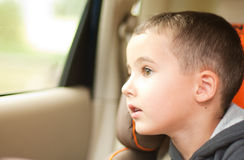 Curious little boy in the car watching the window. Sitting in safe chair Stock Photo