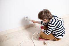 Curious little boy playing with electric plug. Royalty Free Stock Images