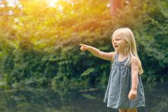Curious little girl in dress pointing at something. Portrait of curious little Caucasian girl wearing blue dress pointing at something outdoors stock photo