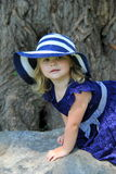 Curious little girl dressed in blue, climbing on big rock Royalty Free Stock Image