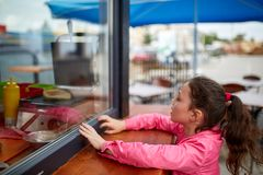 Curious little girl waiting for her burger in the street shop window. Curious little girl in a pink jacket waiting to take away her burger in the street shop royalty free stock photo