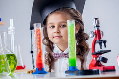 Curious little girl posing with microscope in lab Stock Images