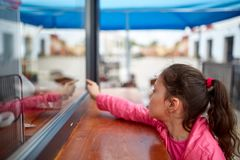 Curious little girl waiting for her burger in the street shop window. Curious little girl in a pink jacket waiting to take away her burger in the street shop stock image