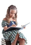 Curious little girl writing in notebook Stock Photography