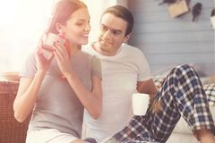 Curious lively girl guessing what inside the box. What is in there. Excited beautiful young women shaking the present while her boyfriend looking at her and Stock Photography