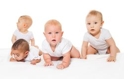 Curious looking babies crawl in a row together Stock Photo