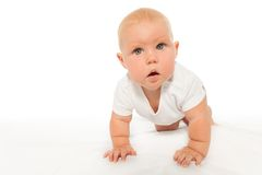 Curious looking baby crawls wearing white bodysuit. On the white background stock photo