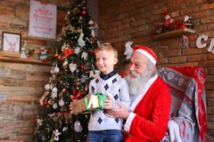 Curious male child receives gift from Santa Claus in decorated f Stock Photos