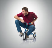 Curious man on a children's bicycle Stock Photo