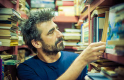 Curious man choosing book between the shelves in the library Royalty Free Stock Photos
