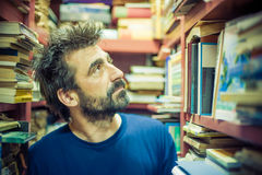 Curious man choosing book between the shelves in the library. Close up Stock Photos