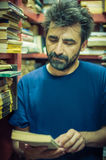 Curious man choosing book between the shelves in the library Royalty Free Stock Images