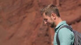 Curious man examining mountains of red limestone formed due to volcanic eruption. Stock footage stock video footage