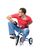 Curious man in glasses on a children's bicycle royalty free stock photo
