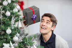 Curious Man Holding Gift By Christmas Tree Stock Photo
