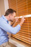Curious man looking through the blinds Stock Images