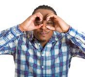 Curious man looking through fingers like binoculars searching Royalty Free Stock Photos