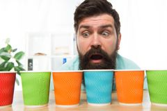 Curious man looks on colorful coffee cups. Color your day. Different types of coffee drinks in cafe menu. large