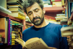 Curious man reading book between the shelves in the library Royalty Free Stock Images