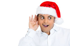 Curious man in red santa hat eavesdropping Royalty Free Stock Images