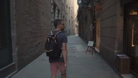 Curious man is traveling in Barcelona, walking in Gothic Quarter in summer day. Bearded male tourist is viewing medieval architecture and small shops in Gothic stock video