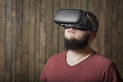 Curious man with vr. Virtual reality glasses. Bearded man with virtual reality glasses standing over wooden background. concept of nosy, curiosity, cognition royalty free stock photo