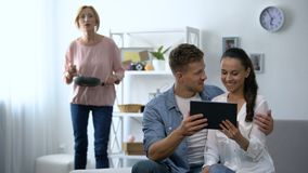 Curious mother-in-law looking young couple scrolling on tablet PC at home. Stock footage stock footage