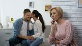 Curious mother-in-law secretly listening woman whispering secret on husband ear. Stock footage stock video footage