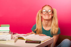 Curious, naughty, playful schoolgirl with hairstyle as Pippi Lon. Gstocking and big eyeglasses making fun out of her while should study. Playing a good girl Stock Images