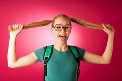 Curious, naughty, playful schoolgirl with hairstyle like Pippi L. Ongstocking, big eyeglasses and backpack, excited to go to school to learn new things and get Stock Images
